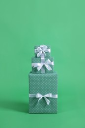 Stack of beautifully wrapped gift boxes on green background