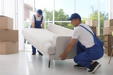 Moving service employees carrying sofa in room