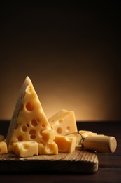 Pieces of delicious cheese and knife on wooden table. Space for text