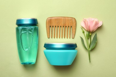 Hair care cosmetic products, wooden comb and flower on light green background, flat lay