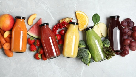 Bottles of delicious juices and fresh fruits on marble table, flat lay
