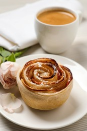 Freshly baked apple rose, cup of coffee and beautiful flowers on white wooden table