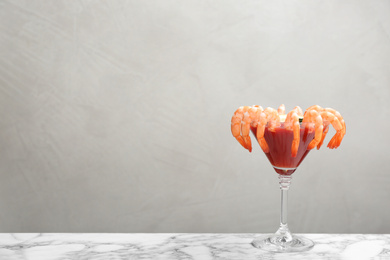 Shrimp cocktail with tomato sauce on marble table. Space for text