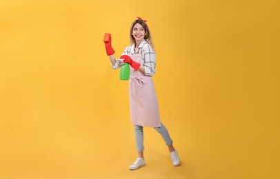 Young housewife with detergent and sponge on yellow background