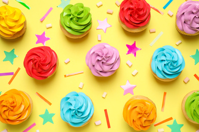 Colorful birthday cupcakes on yellow background, flat lay