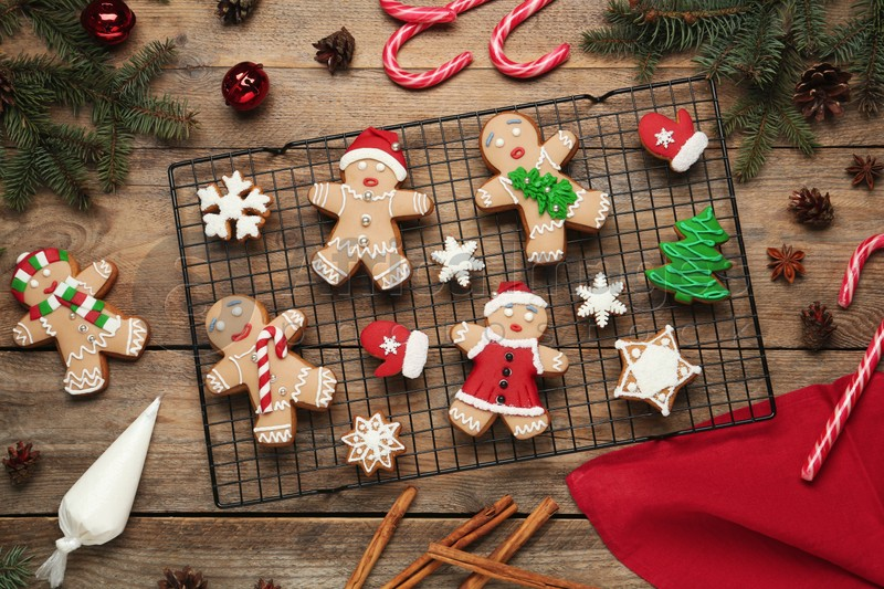 Delicious Christmas cookies and festive decor on wooden table, flat lay