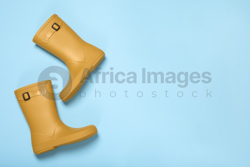 Pair of yellow rubber boots on light blue background, top view. Space for text