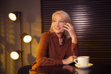 Beautiful mature woman with cup of coffee talking on smartphone indoors