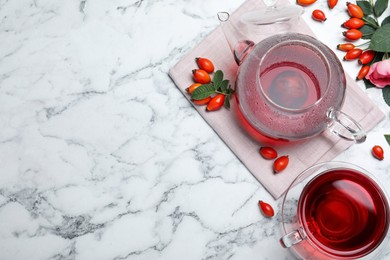 Fresh rose hip tea and berries on white marble table, flat lay. Space for text
