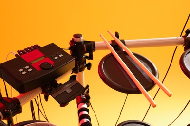 Modern electronic drum kit on yellow background. Musical instrument