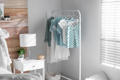 Rack with stylish women's clothes in modern room. Interior design
