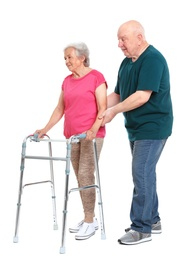 Elderly man helping his wife with walking frame on white background