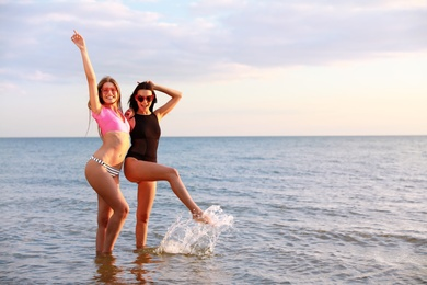 Young woman in bikini with girlfriend on beach. Lovely couple
