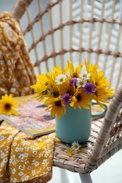 Beautiful bright flowers in light blue cup near magazine and fabric on rattan armchair