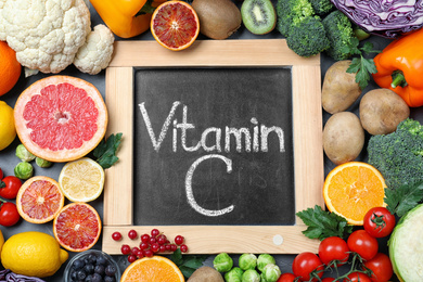 Different products and blackboard with phrase VITAMIN C on table