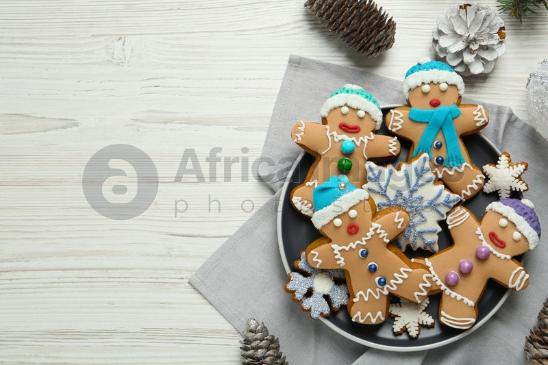 Delicious Christmas cookies and pine cones on white wooden table, flat lay. Space for text