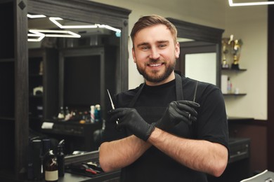 Happy hairdresser with professional tools in barbershop