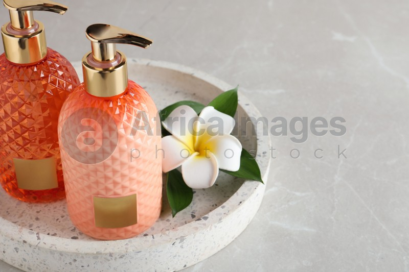 Cosmetic products and flower on light table. Space for text