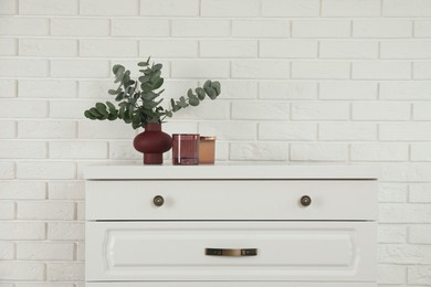 Modern chest of drawers with decor near white brick wall