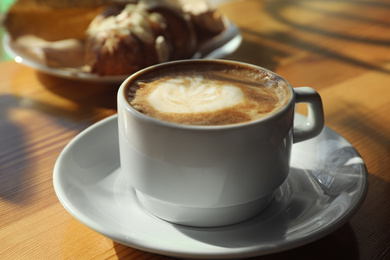 Cup of fresh aromatic coffee at table in cafe