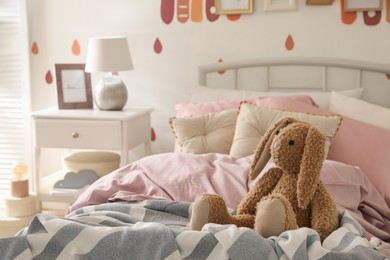 Toy bunny on bed in child's room. Interior design
