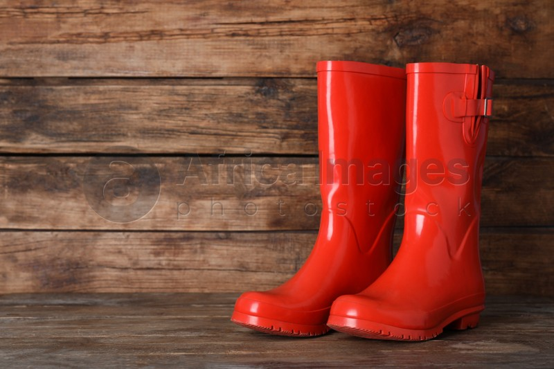 Pair of red rubber boots on wooden surface. Space for text