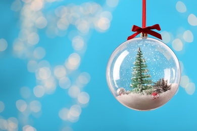 Decorative snow globe hanging on against blurred festive lights, closeup. Space for text
