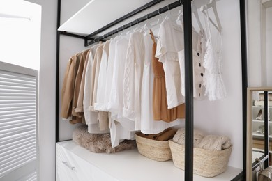 Rack with stylish women's clothes in dressing room