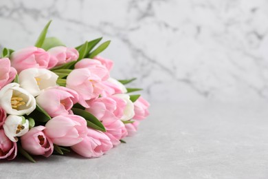 Beautiful bouquet of tulips on light table. Space for text