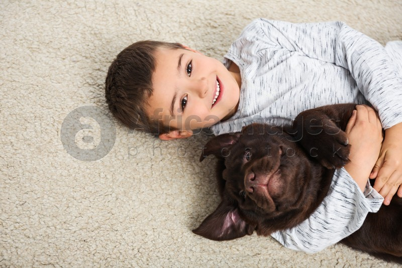 Little boy with dog lying on floor, top view