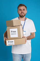 Male courier holding parcels with stickers Free Delivery on light blue background