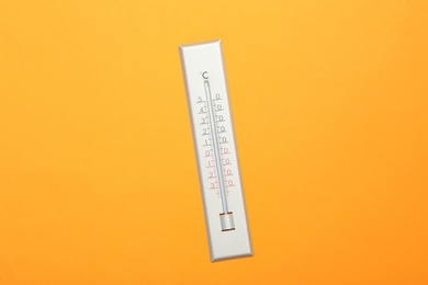 Weather thermometer on orange background, top view