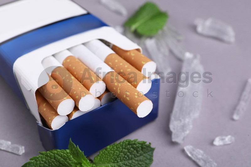 Pack of cigarettes, menthol crystals and mint leaves on grey background, closeup