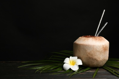 Fresh coconut with drinking straws and flower on wooden table against black background. Space for text