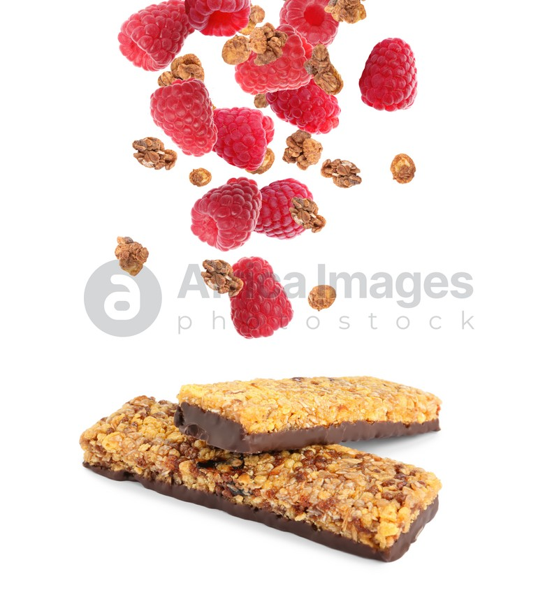 Tasty protein bars and granola with raspberries falling on white background
