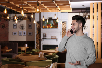 Young business owner talking on phone in his cafe. Space for text