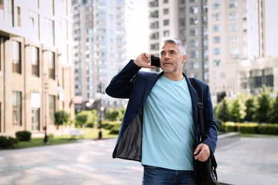 Portrait of handsome mature man talking on phone in city center. Space for text