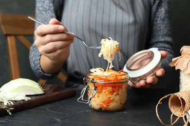 Woman eating fermented cabbage at black table, closeup