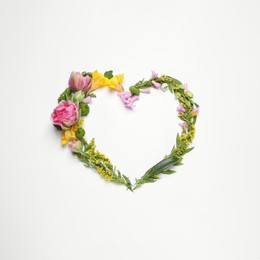Beautiful heart made of different flowers on white background, top view