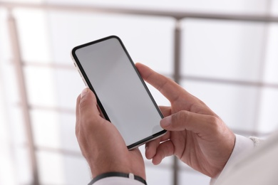 Man holding mobile phone with empty screen indoors, closeup