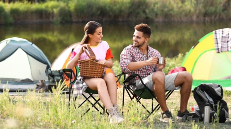 Young couple having picnic near camping tent