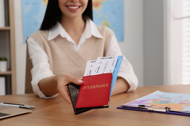 Travel agent with tickets and passports at table in office, closeup