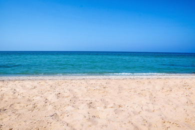 Beautiful view of sandy beach and sea on sunny day
