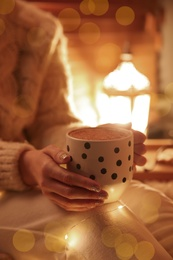 Woman with cup of hot drink at home, closeup. Christmas celebration
