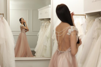 Woman trying on wedding dress in boutique