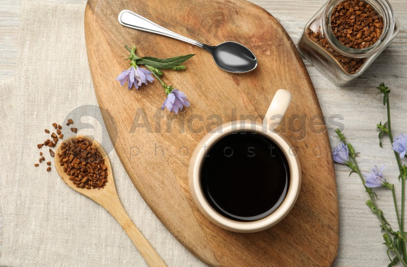 Flat lay composition with delicious chicory drink, granules and flowers on table