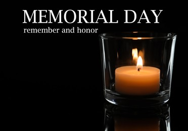 Memorial day. Wax candle burning on black background