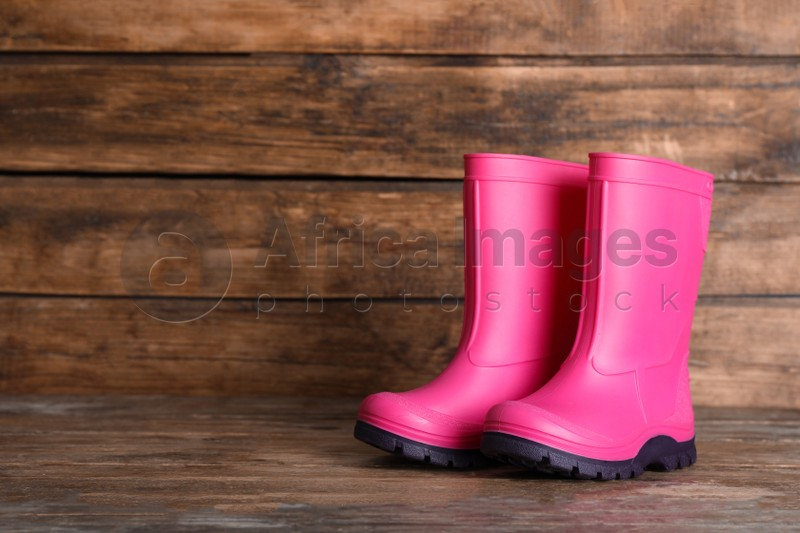 Pair of bright pink rubber boots on wooden surface. Space for text