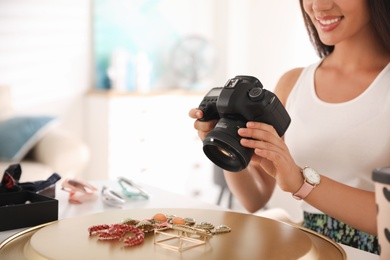 Young photographer taking picture of jewelry indoors, closeup