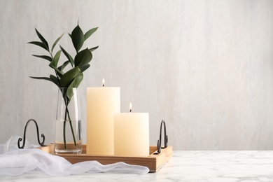 Beautiful burning candles and vase with green branches on white marble table. Space for text